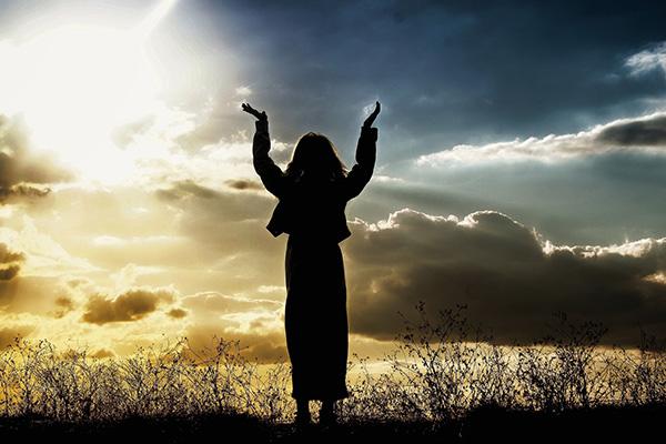 Mujer orando en el campo.
